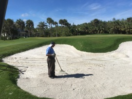 Miguel measuring bunker depths and adding sand to green side bunkers